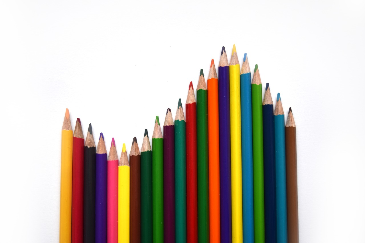 Vertical row of multi-colored pencils, arranged in a decreasing then increasing and finally a decreasing pattern.
