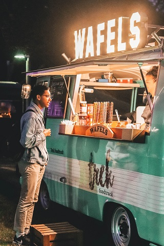 Man ordering from green and white striped food truck.