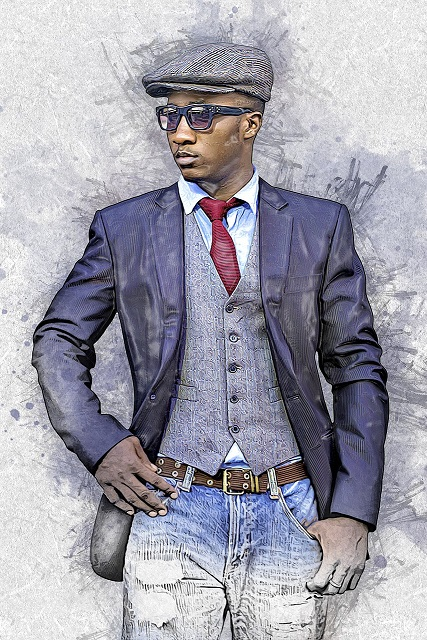 Young Black male stylishly dressed, standing with one hand in his pocket.